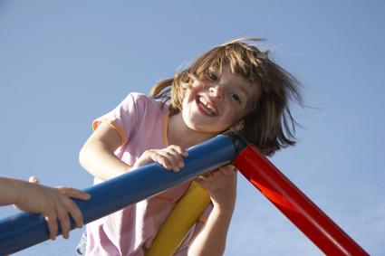 Kinderfoto mit jungem Mädchen auf dem Spielplatz ideal für ein eigenes Fotobuch